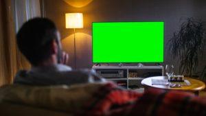 mann schaut auf einen fernseher mit gruenem bildschirm