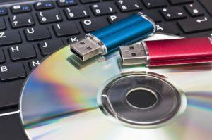 cds und usb-sticks vor einer tastatur